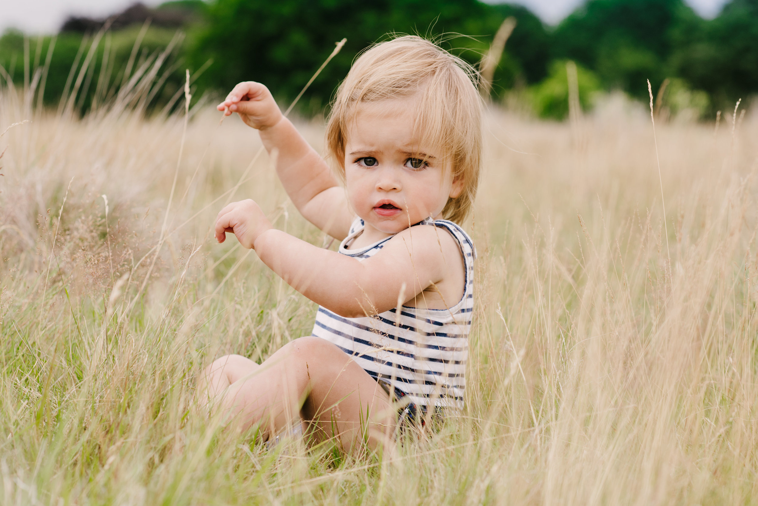 little girl sat playing with the long grass in the park | Children's Photographer Aylesbury Buckinghamshire and Thame Oxfordshire