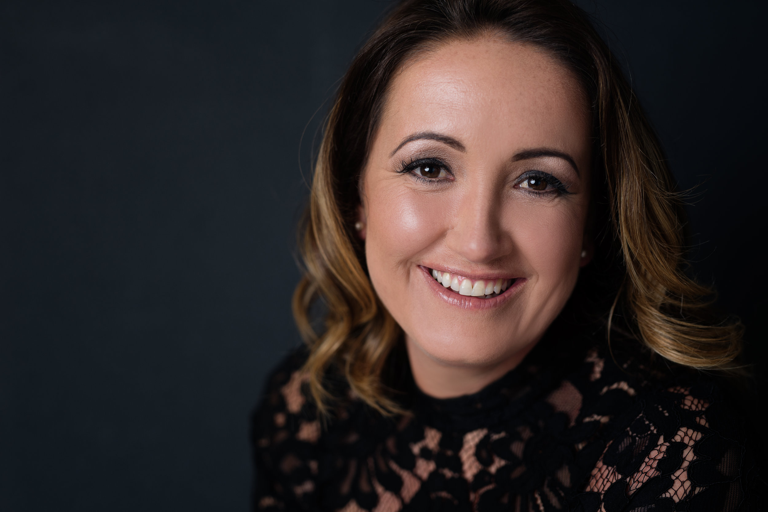 Headshot of a lady smiling wearing black lace top with a dark grey background in studio | Corporate Photographer Aylesbury Buckinghamshire and Thame Oxfordshire