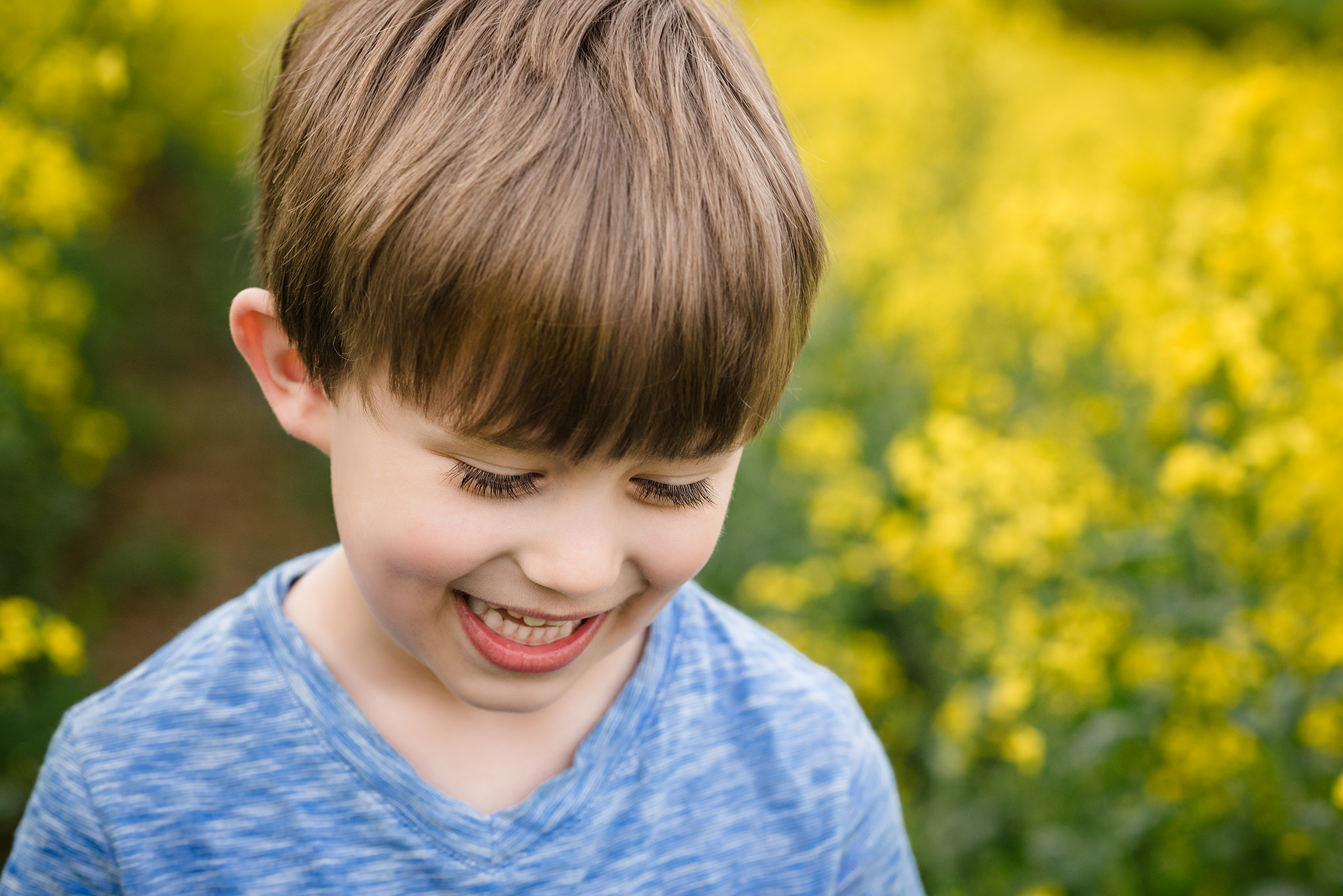 Close up of a little boy looking down smiling in a rapeseed field on a photography session in buckinghamshire