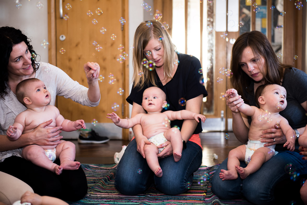 3 young mothers kneeling on the floor with their babies sitting on their laps catching bubbles