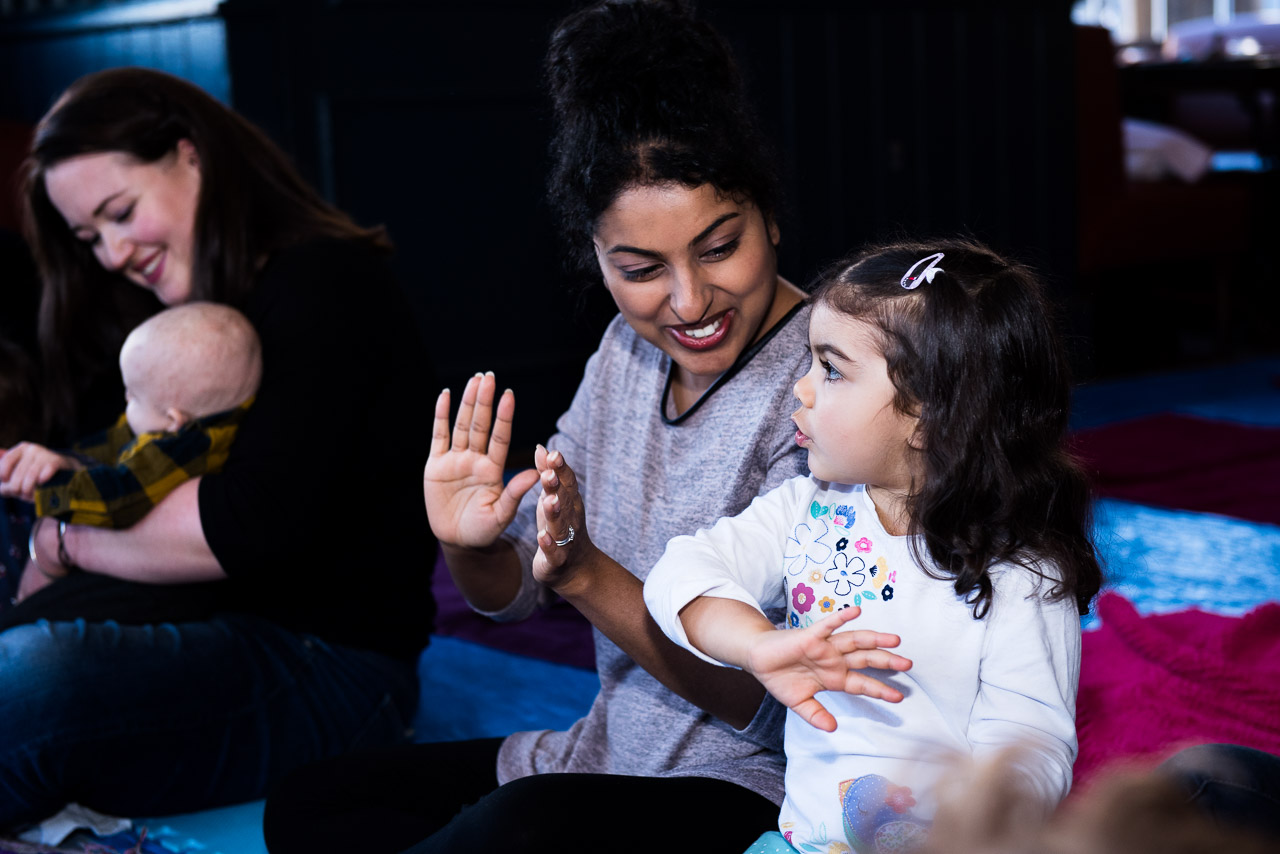 Little girl singing and dancing with her mother