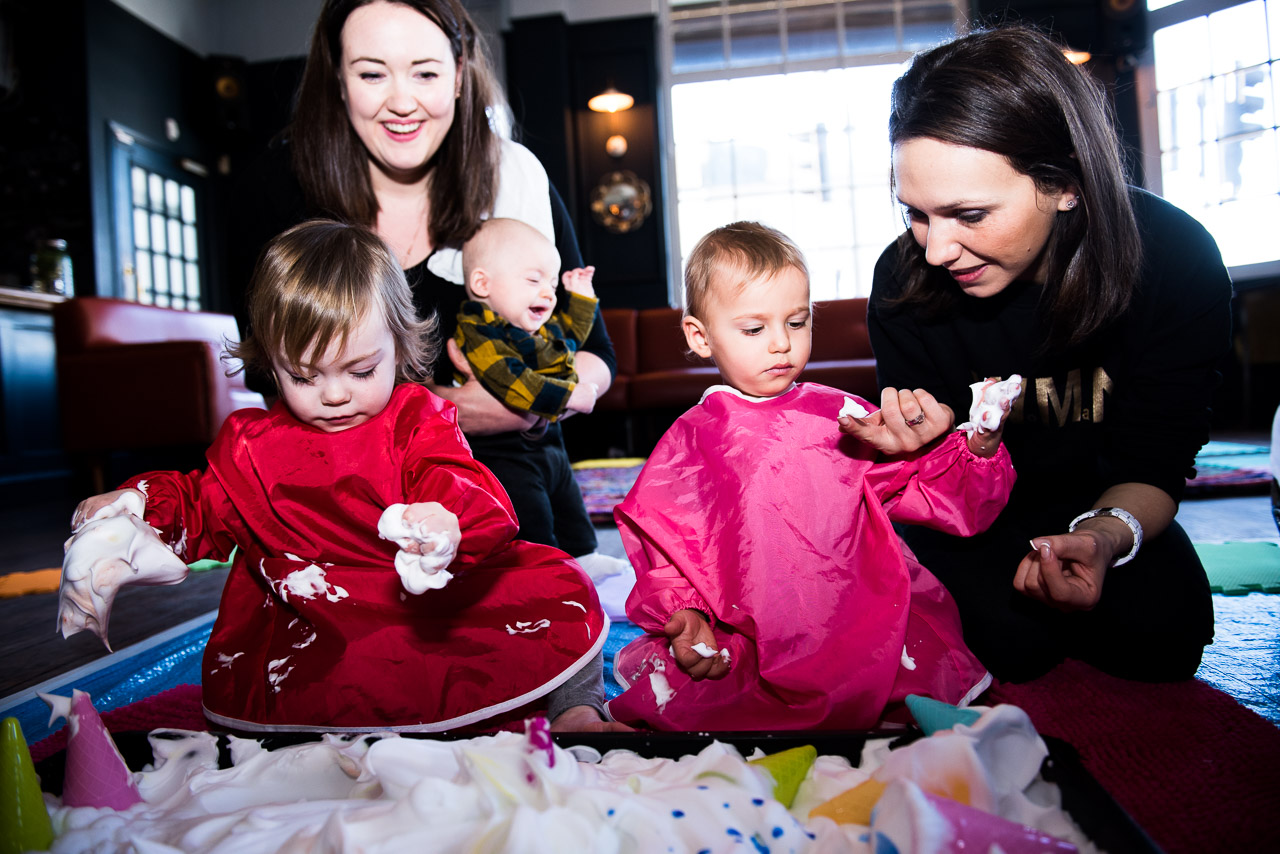 Two little girls playing in messy play tray with their mothers