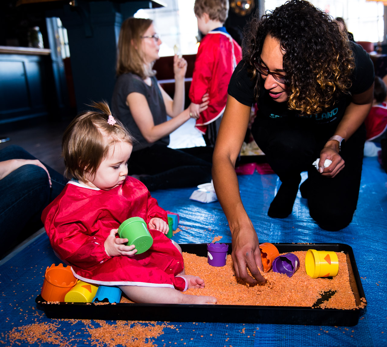 Little girl sitting in messy play tray filled with lentils