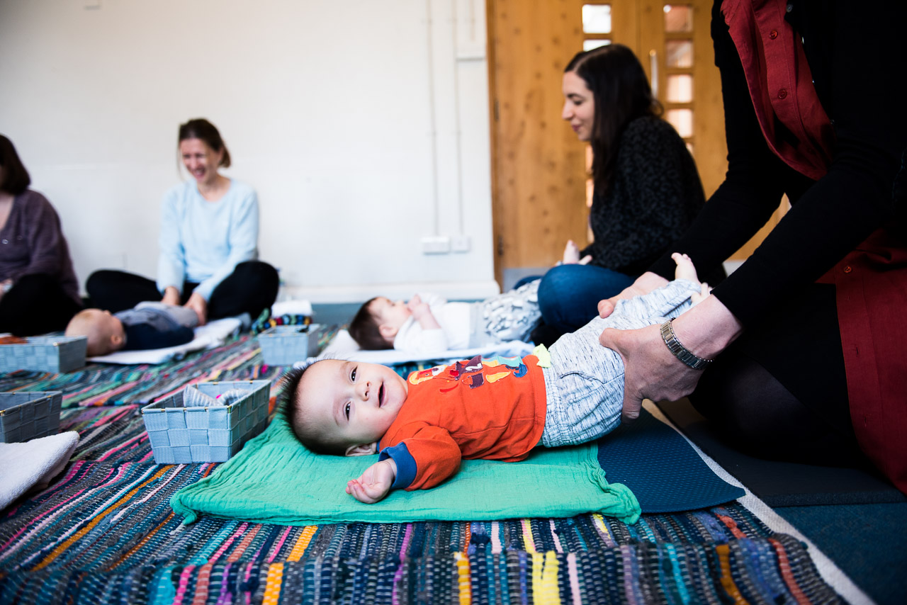 Smiling baby boy being stretched in baby yoga class