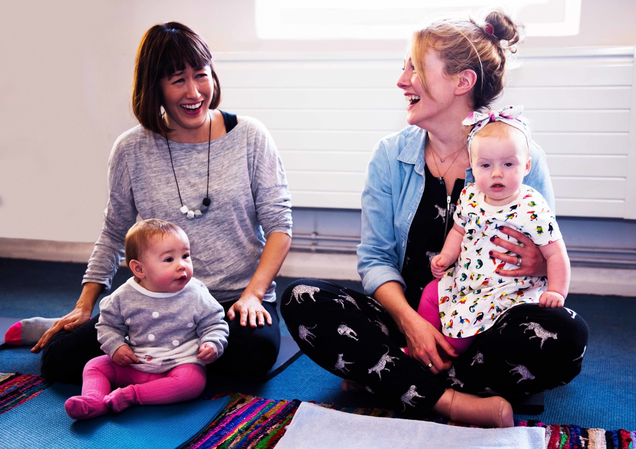 2 mothers laughing during baby yoga class