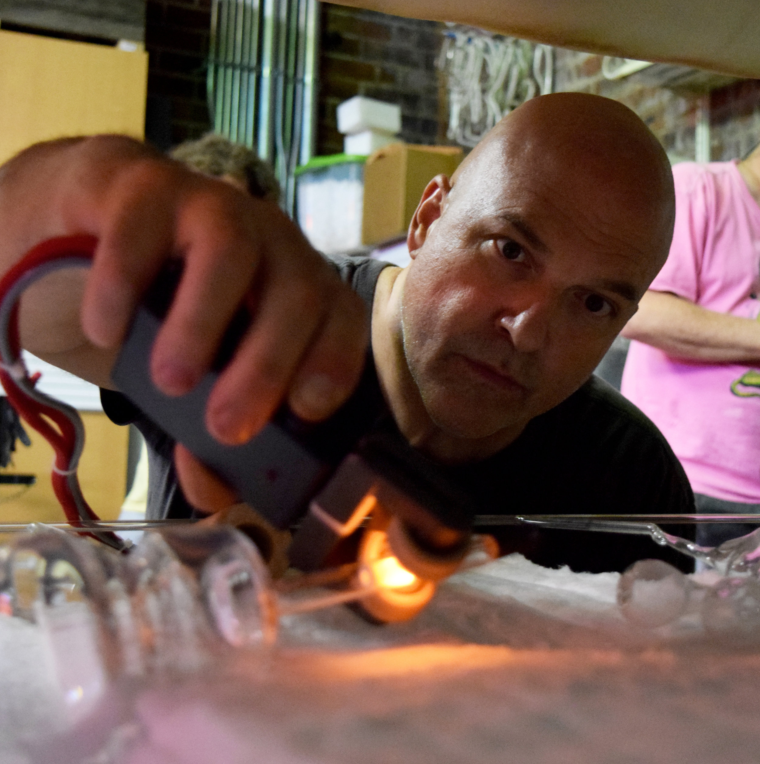 "Nate Sheaffer - Nate is the father of Glas. His 30+ years as a neon artist has made him dedicated to bolstering the appreciation, knowledge, and manufacturing of American Neon.After graduating from UNC-Chapel Hill in the late 80's, Sheaffer was inspired to begin specializing in installations featuring neon lighting. His distinctive style consists of adding colorful neon wording and designs to found objects, sculptures, and canvases.""…the goal is to draw awareness to ways we all can be more thoughtful in multi-purpose usefulness of the planet's natural resources"" – Nate Sheaffer"