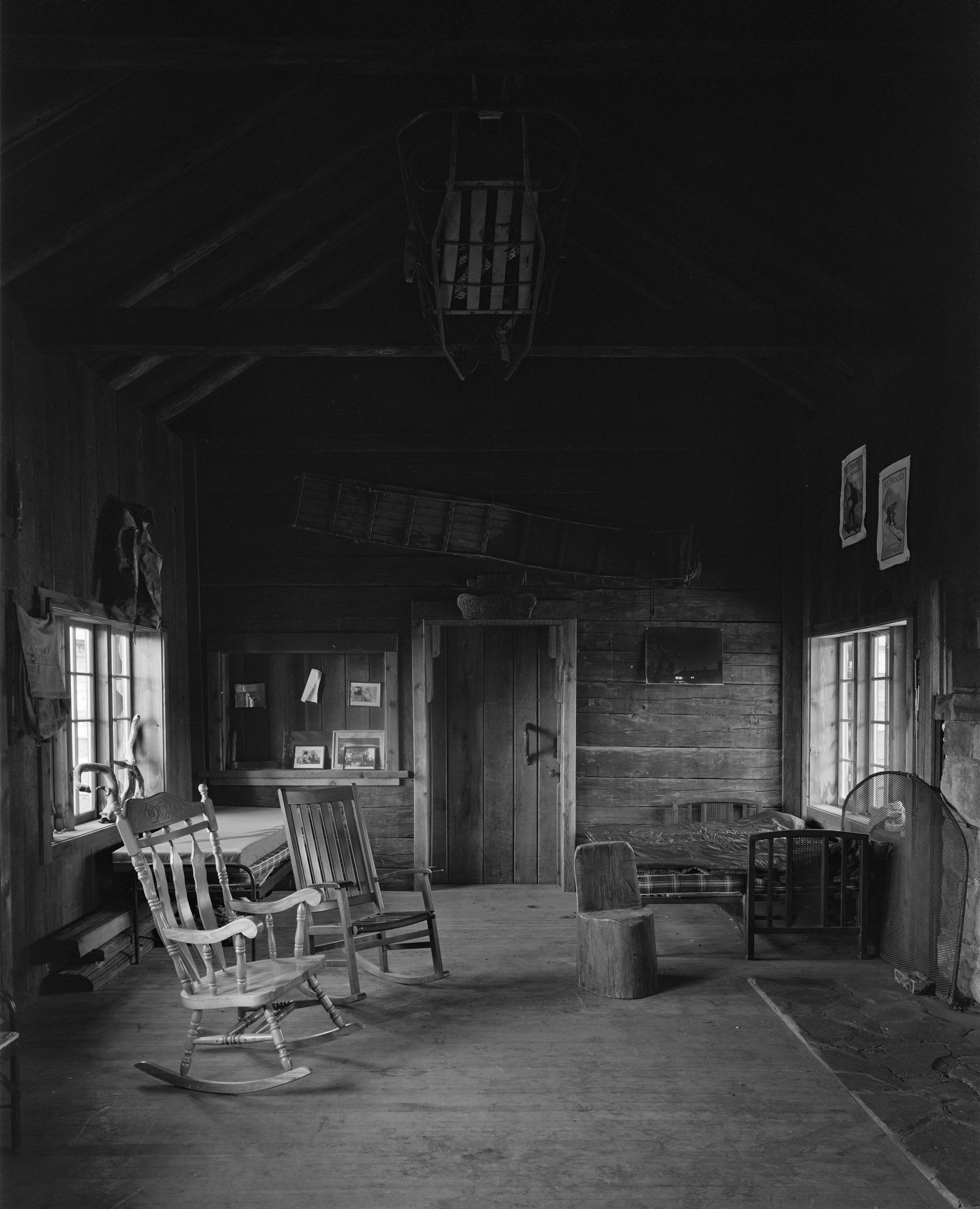 The central living room has an original and fully functional stone fireplace. The door seen here leads to the guest wing. The far wall is made of original planking from 1889 but siding on the wall at the left was replaced in the 1930s by the Civilian Conservation Corps (CCC). Old rescue sleds decorate the wall and roof beams.
