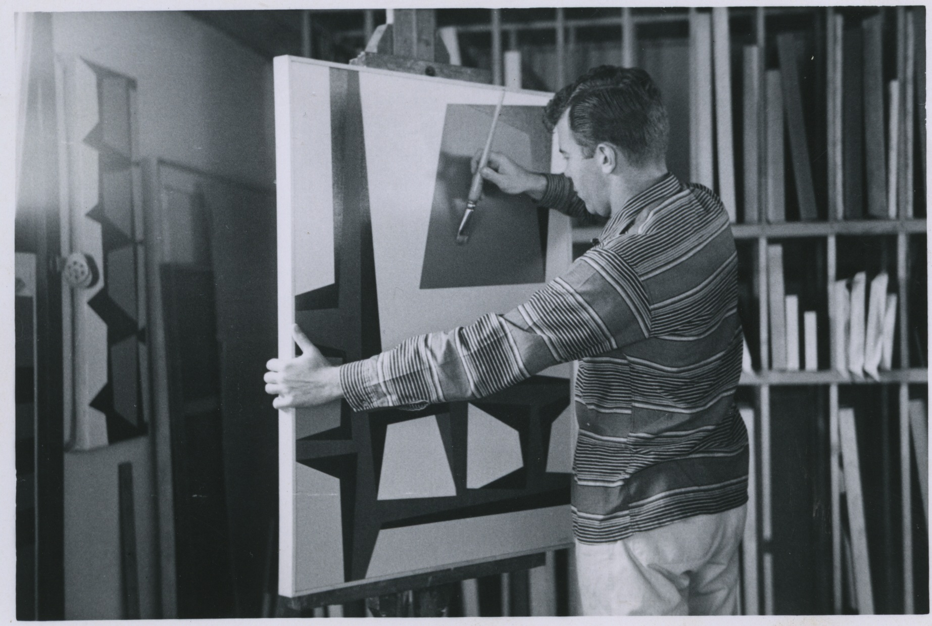 "Karl Benjamin in his studio, painting ""Green Moon with Windows,"" 1957."