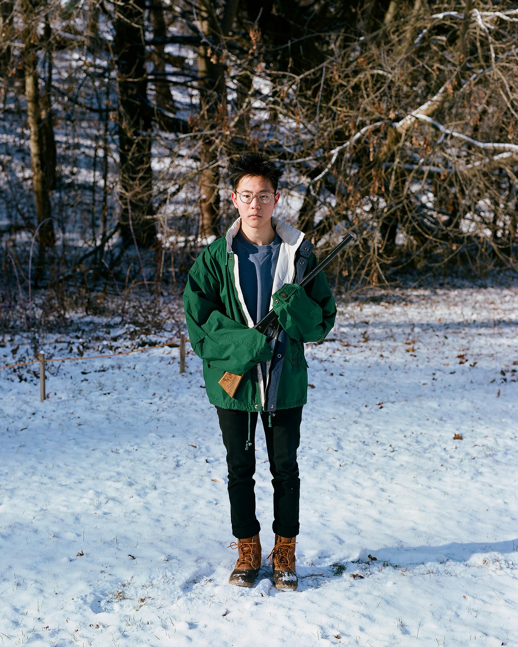 Me wearing Dad's coat holding my old bb gun