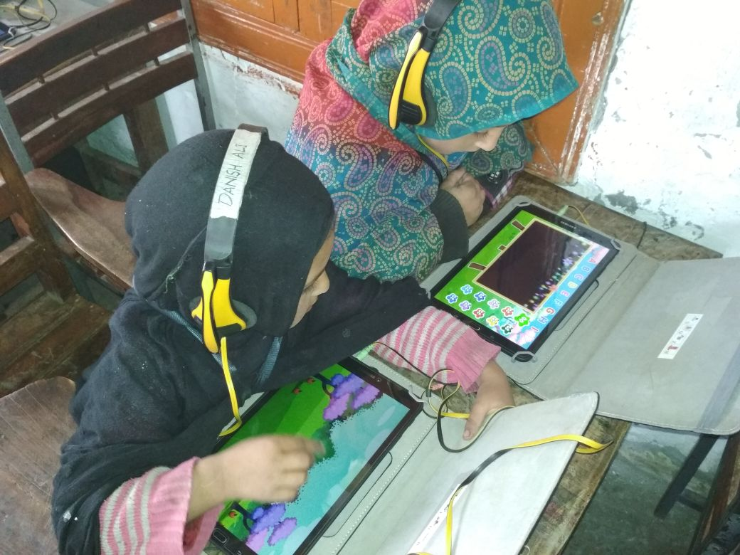 Danish is interested in what her friend Abeeah is learning. The girls are learning in a digital classroom in Sultanabad Village in Basho Valley.