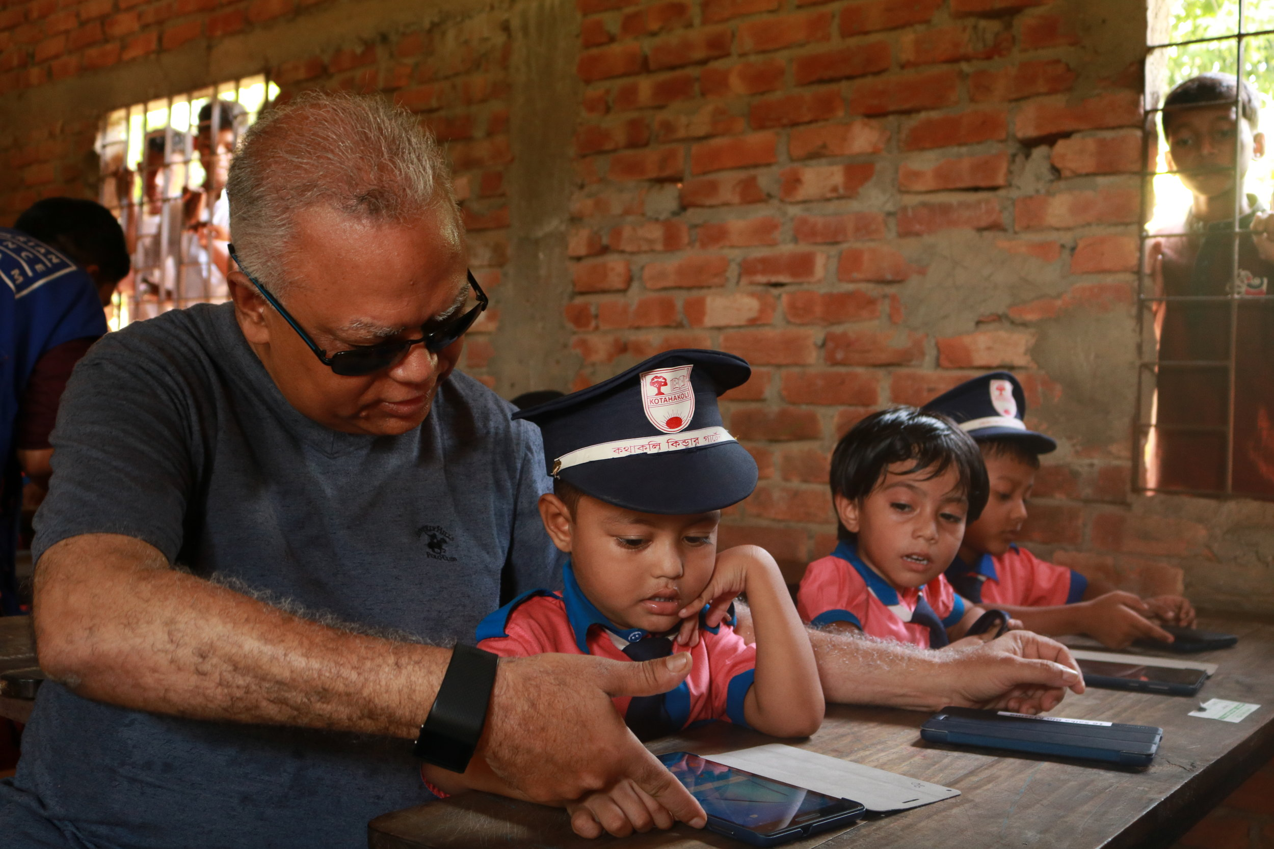 OBAT Helpers CEO Anwar Khan assists a young student during a site visit