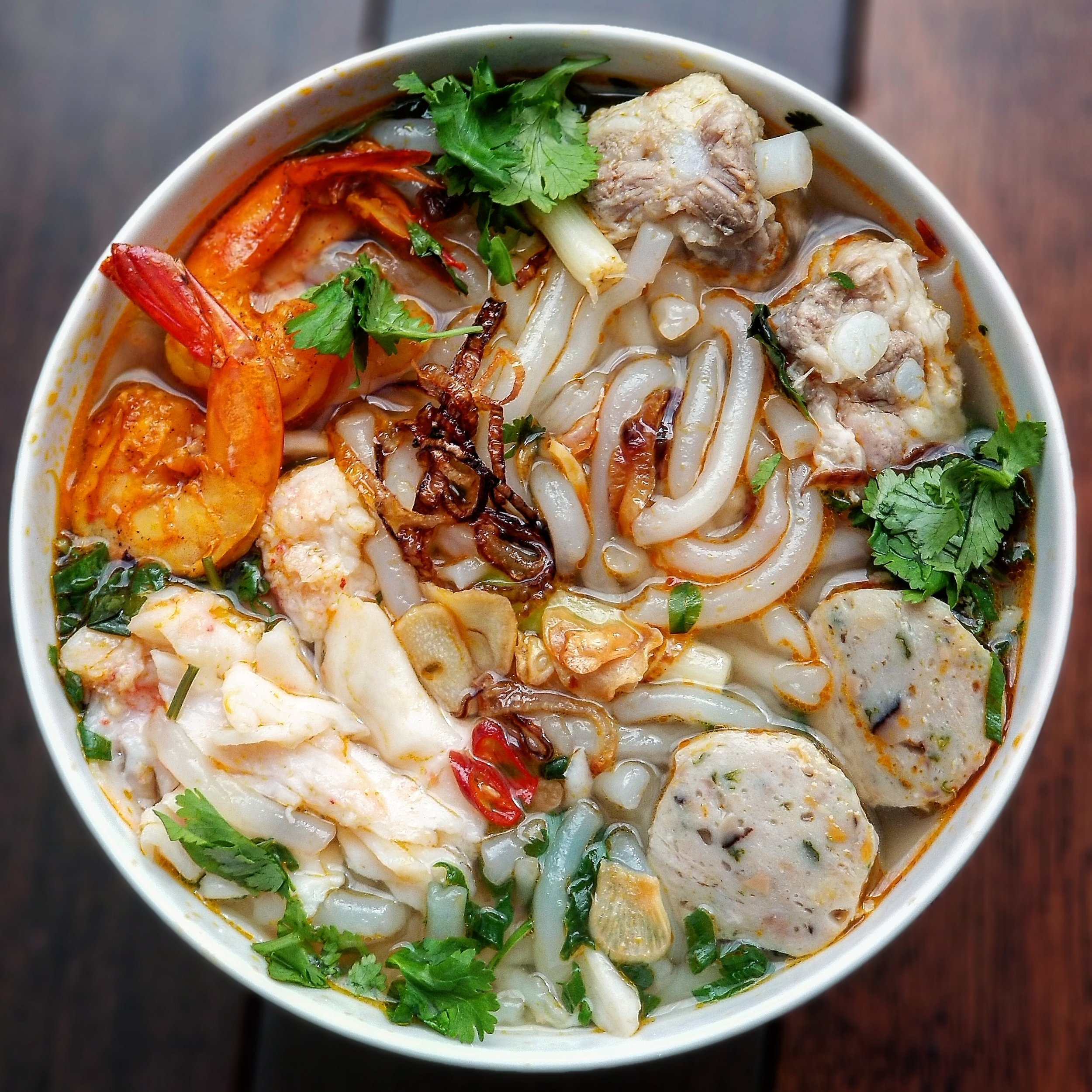 Bánh Canh Tôm Cua Chả Cá - Tapioca noodles in a pork and shrimp broth with shrimp, crab, fish cakes, fried garlic chips, fried shallots, scallion, cilantro and a bit of spicy saté chili paste