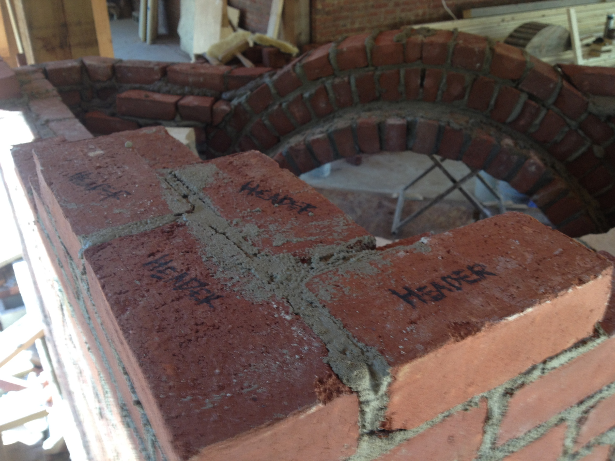 structural masonry, written reminder of the all important header course coming up on a fireplace