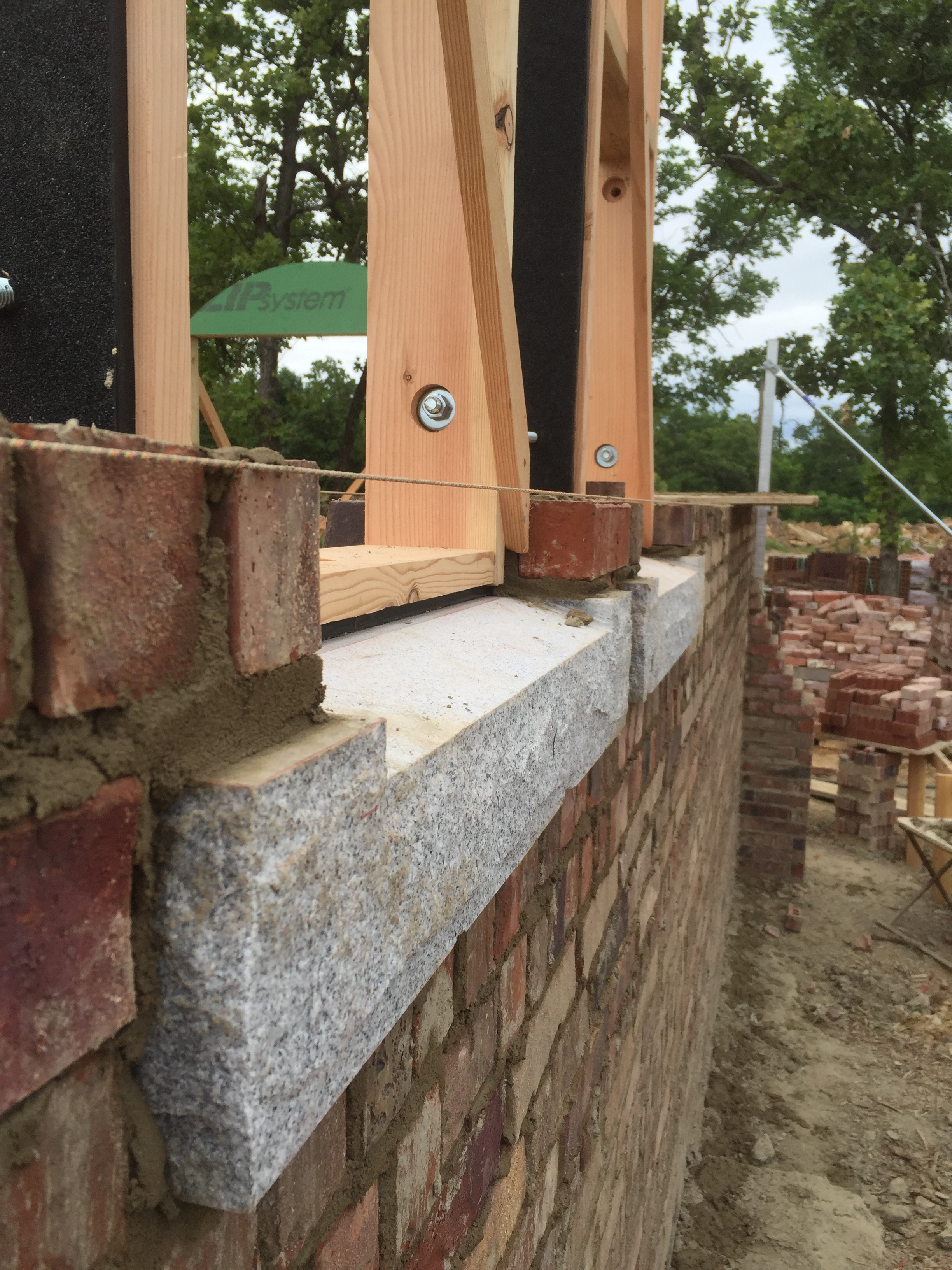 structural masonry, granite window sill with handmade window bucks on top