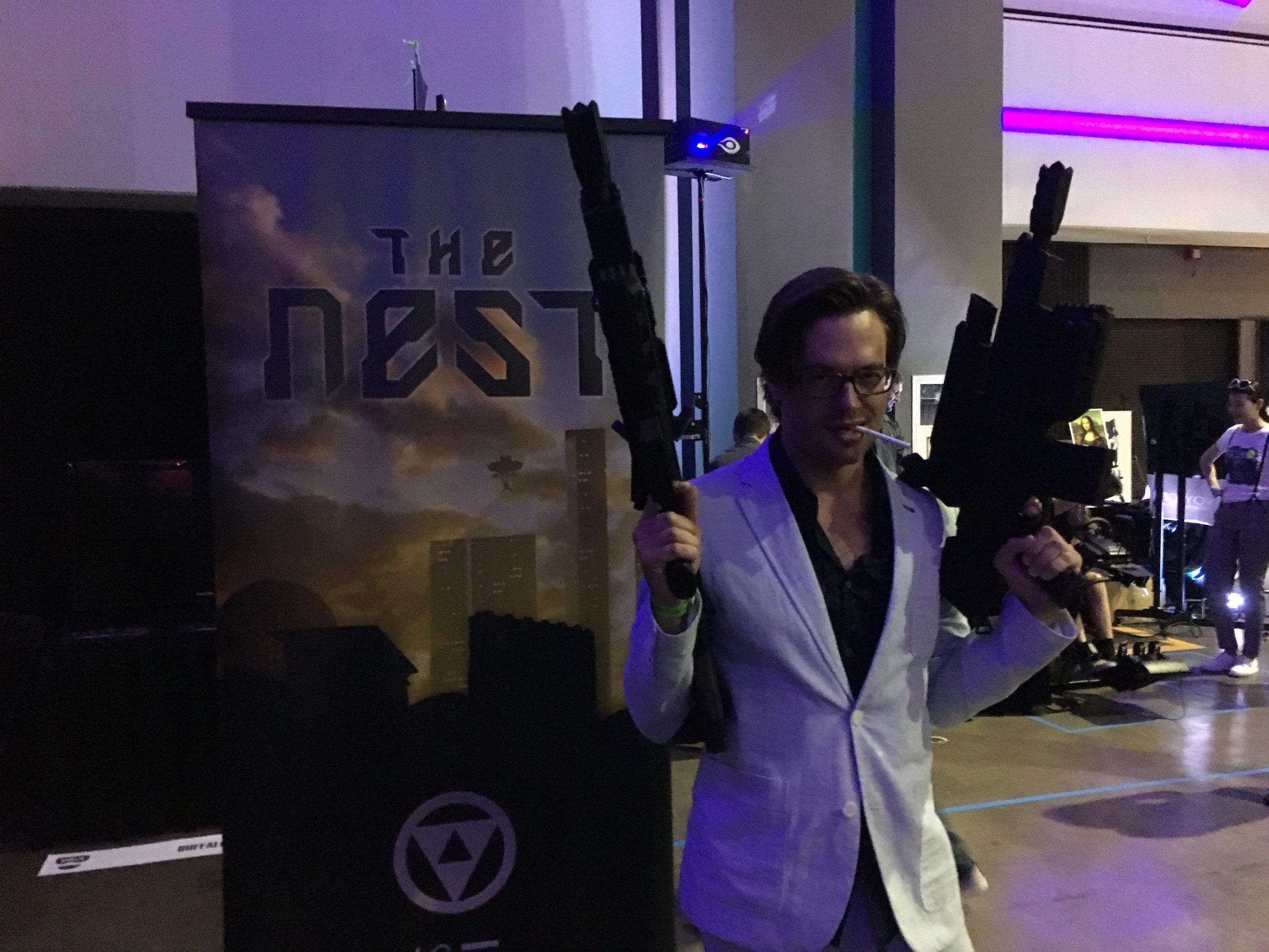 Hunter with the VRsenal guns in front of The Nest display at VRLA