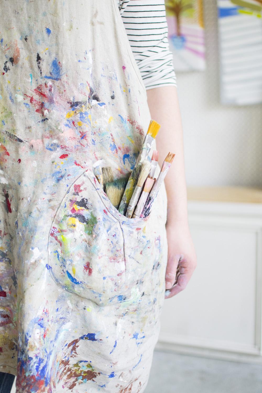 paintbrushes in smock pocket.jpg