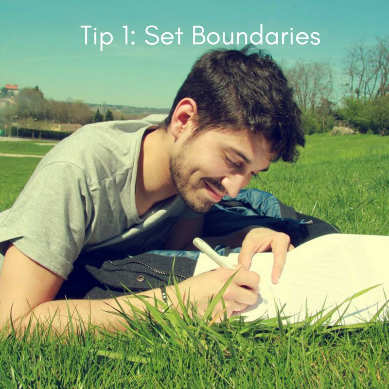 Image description: a man lies on grass smiling while writing in a journal. White text reads 'Tip 1: Set Boundaries'