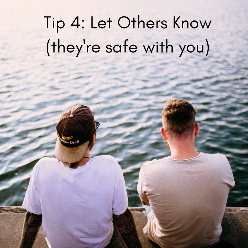Image description: two men sit next to each other with their backs to the viewer on a concrete slab against water. Black text reads 'Tip 4: Let Others Know (they are safe with you)'