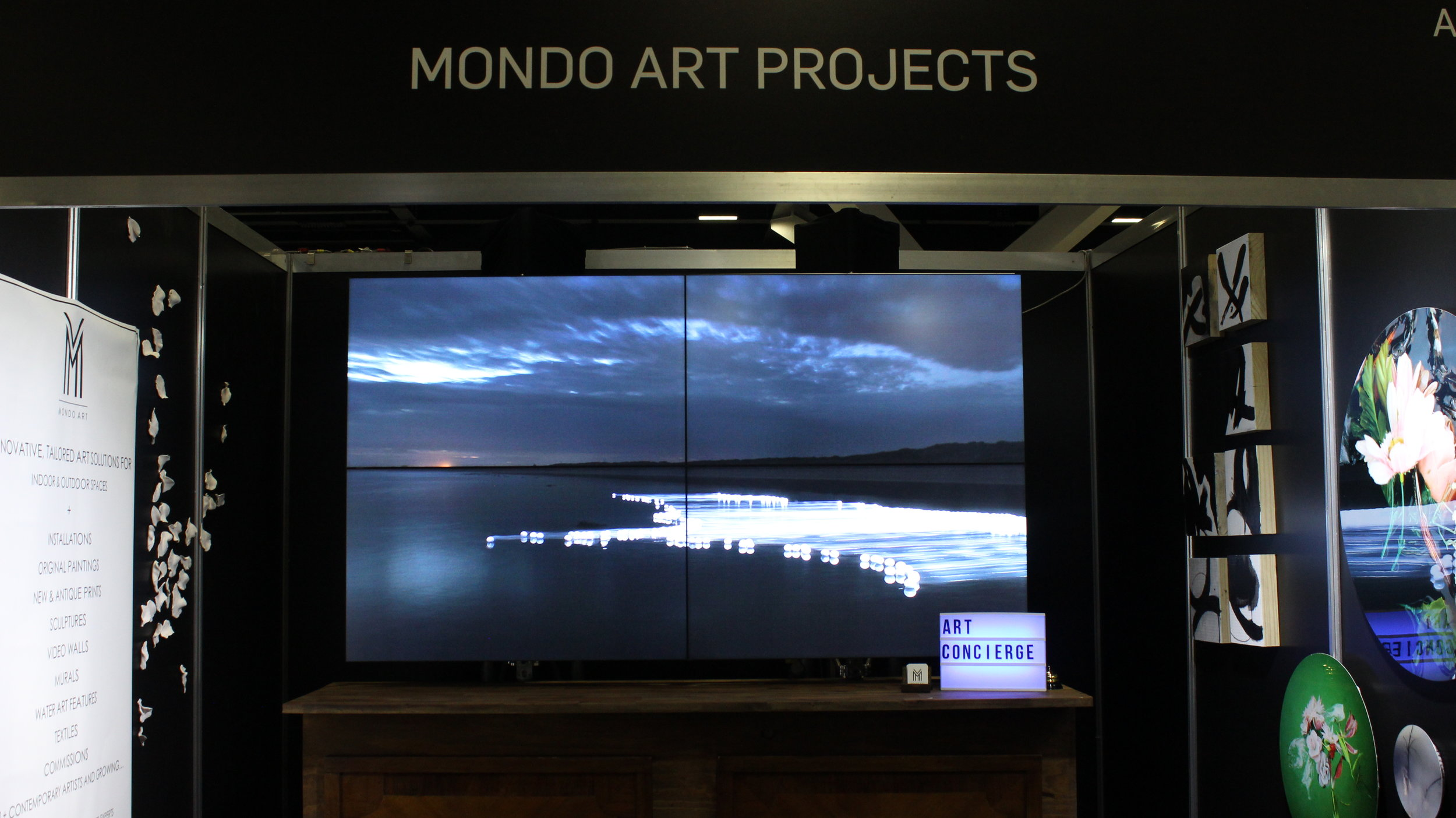 MONDO Art Projects' stand with the largest video wall we could find. Displayed is James Tapscott's and hanging alongside it is Kim Percy with her series of photographs printed onto metal discs.