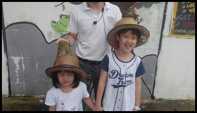 The children were delighted to strike a pose with the bullfrogs on their heads.