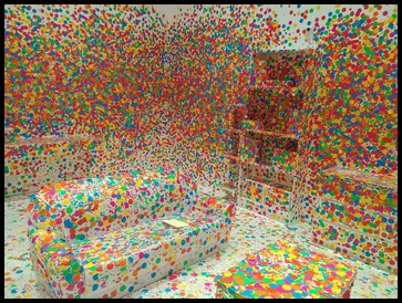 "The second exhibit is named The Obliteration Room by Yayoi Kusama. She is a renowned artist who creates different art pieces by using dots to cover surfaces and fill rooms. She calls it ""obliteration"" which means complete destruction of every trace of something. What can you spot in the picture?"