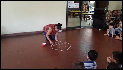 She started by creating a grid with the rangoli powder. This enabled her to create an even octagon.