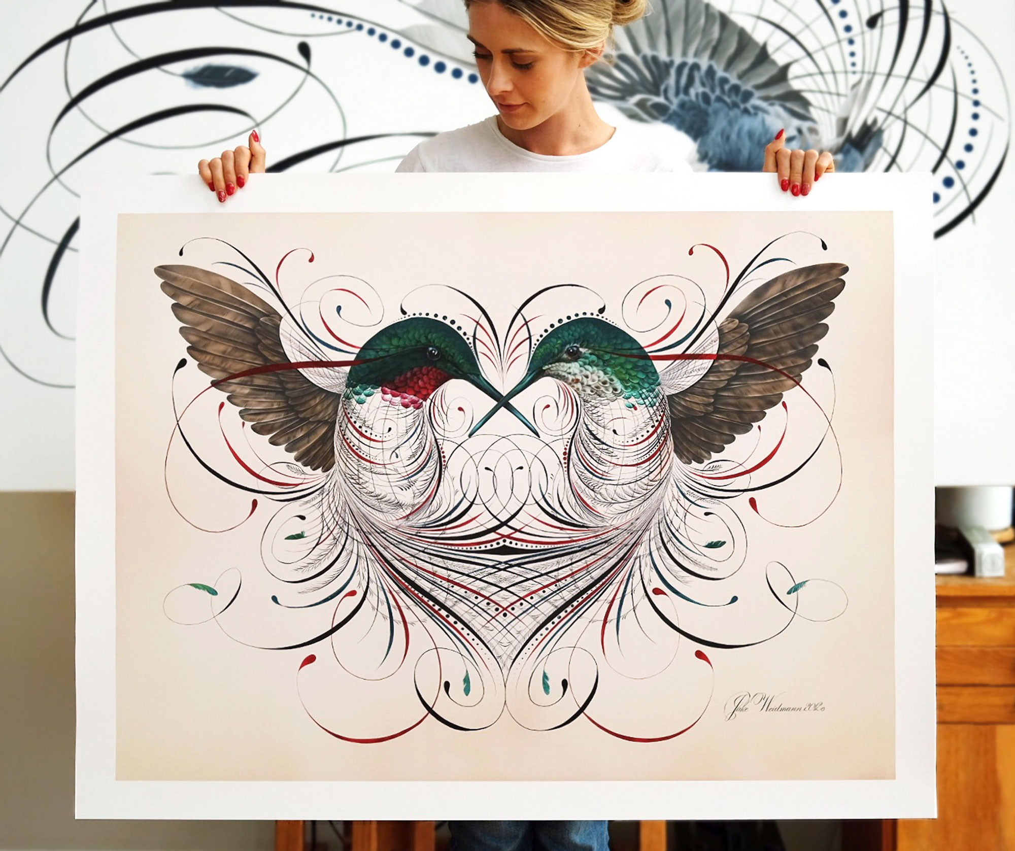 """Hannah Weidmann holds husband Jake's """"Humming a Love Song."""" Gouache and acrylic. 2012.  The hummingbird is romanticized in this design as it pays tribute to the vintage technique of off-hand flourishing. Like the hummingbird, the power of this message is in its details. The entanglement of line work speaks to the essence of love in combining two separate bodies, male and female, as a unified whole. Small imperfections grafted into the symmetry establish its own perfection."""