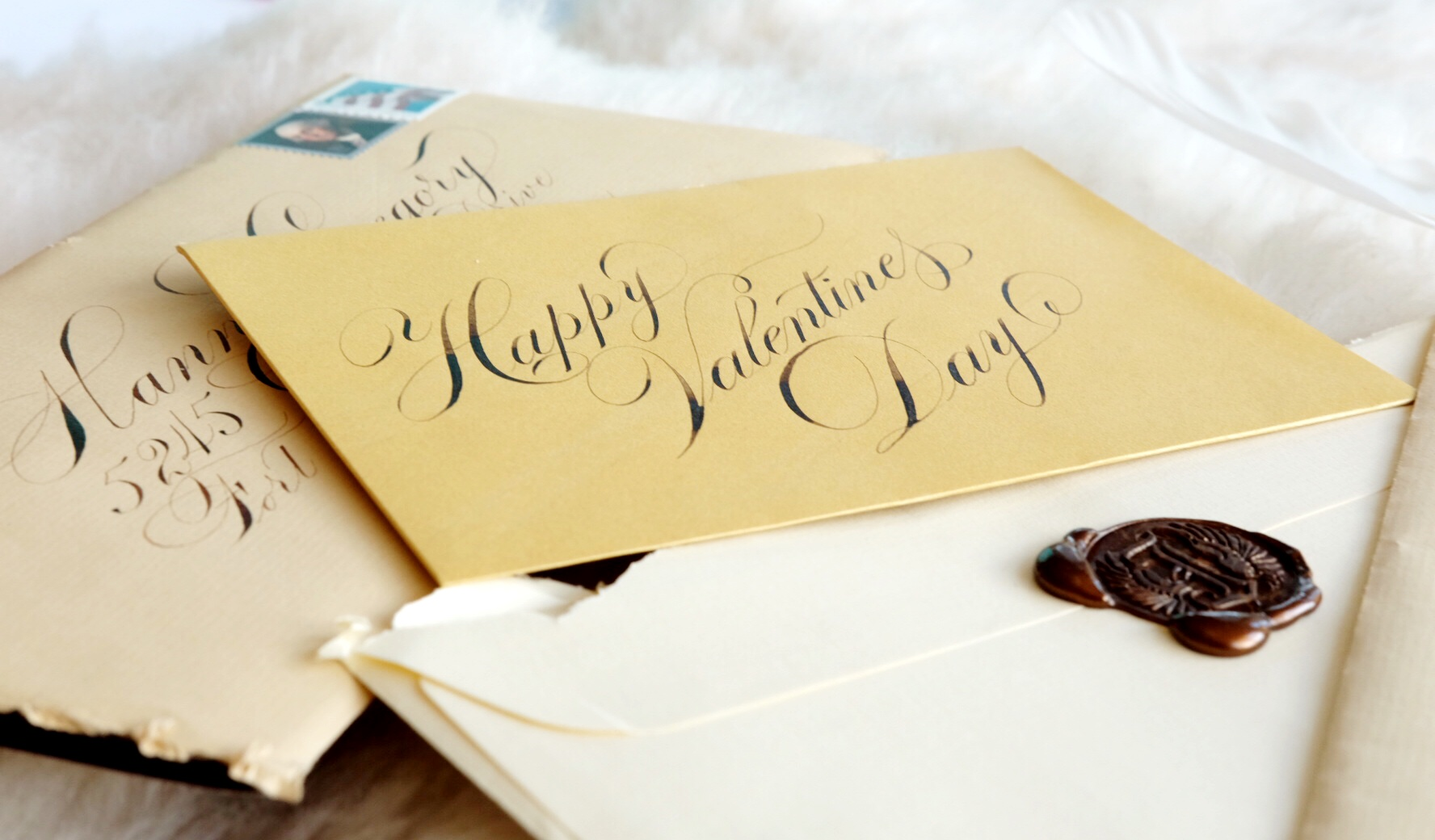 """Jake designed his own wax seal: the letter """"J"""" accompanied by a pair of wings. Each one of his letters to Hannah is sealed with his custom seal in wax that matches the letter's stationery."""