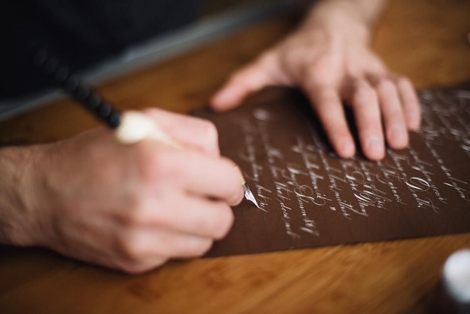 """Hannah caught Jake writing this love letter in white ink on brown paper. It begins, """"My Darling Fiance""""..."""