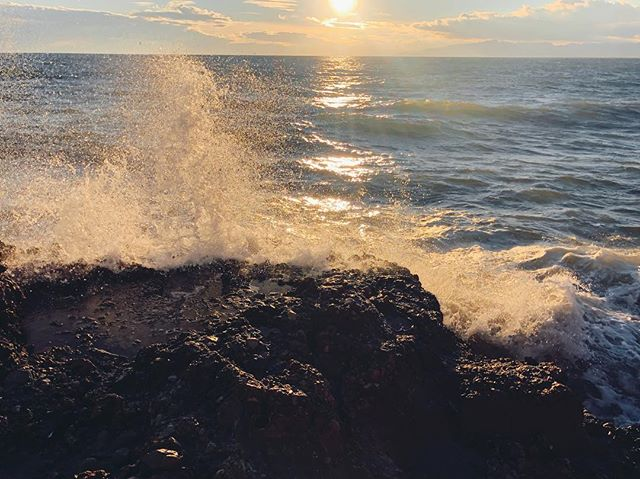 The best way to view a sun set is through the mist of waves crashing against the shore