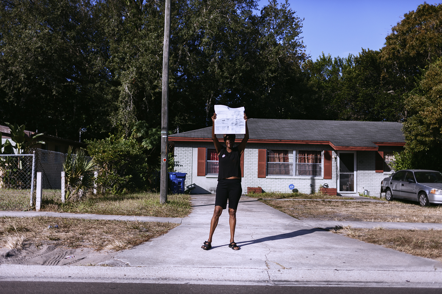 """""""May God bless us today"""", the women screamed as she held an election ballot. Front house wars. Tampa, Fl. 2016"""