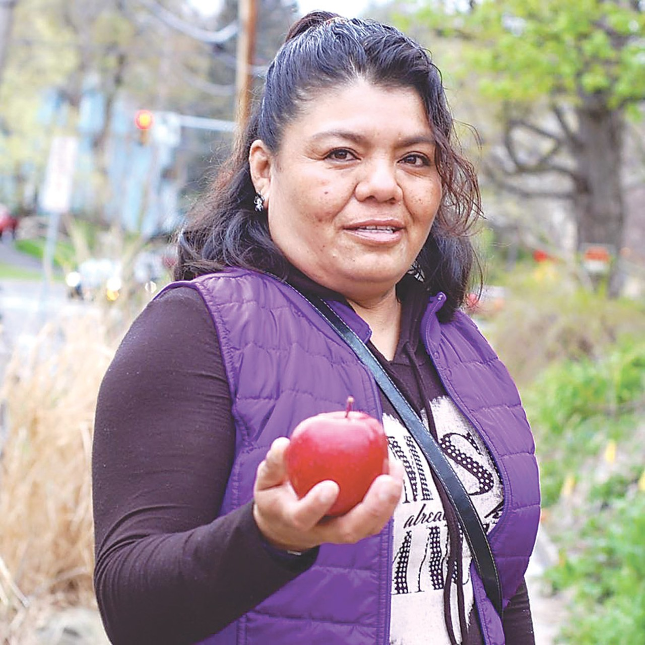 Dolores Bustamante holds an apple. Source:  Rochester City Newspaper
