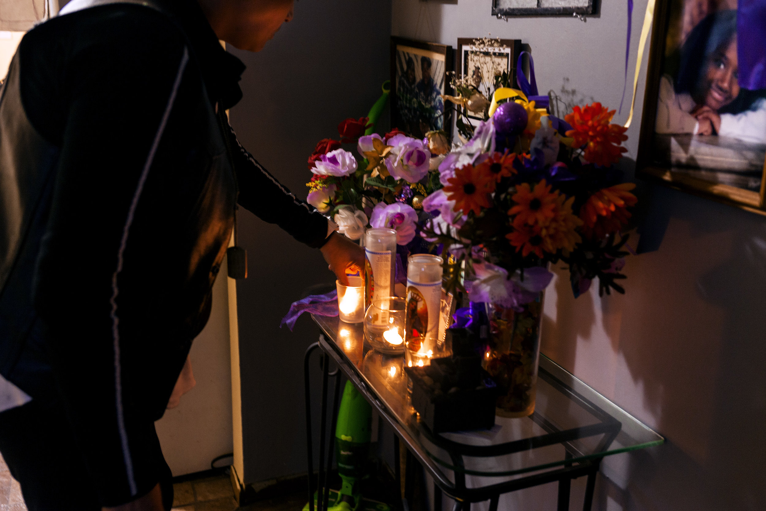 Elizabeth Alvarado, Nisa Micken's mother, lights a candle for Nisa's shrine in their Brentwood home.