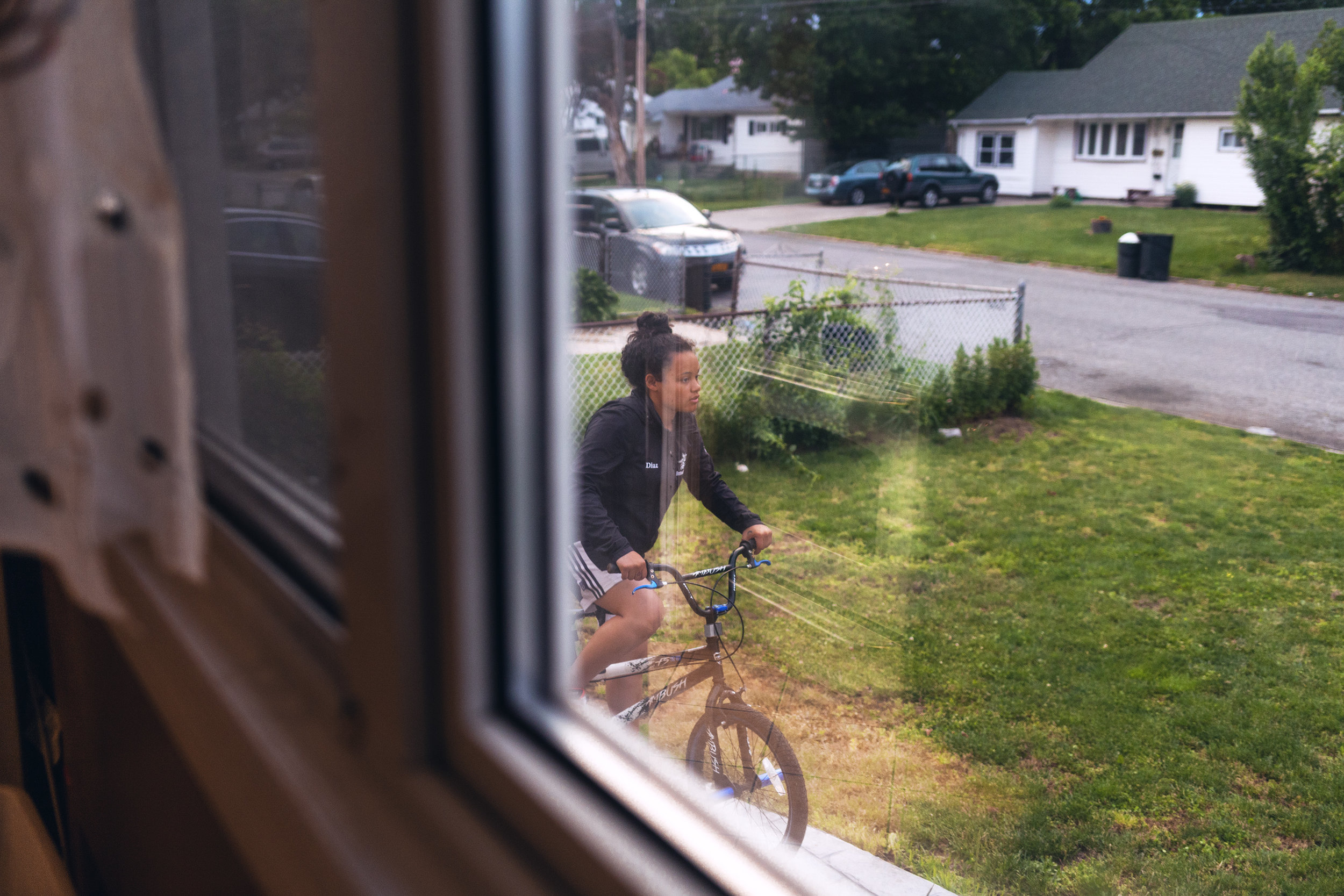Madeline Diaz rides a bike on her porch in Brentwood.