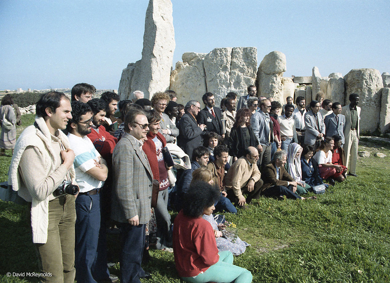 Conference attendees pose for a group photo. Daniel Ellsberg is in front in brown jacket.