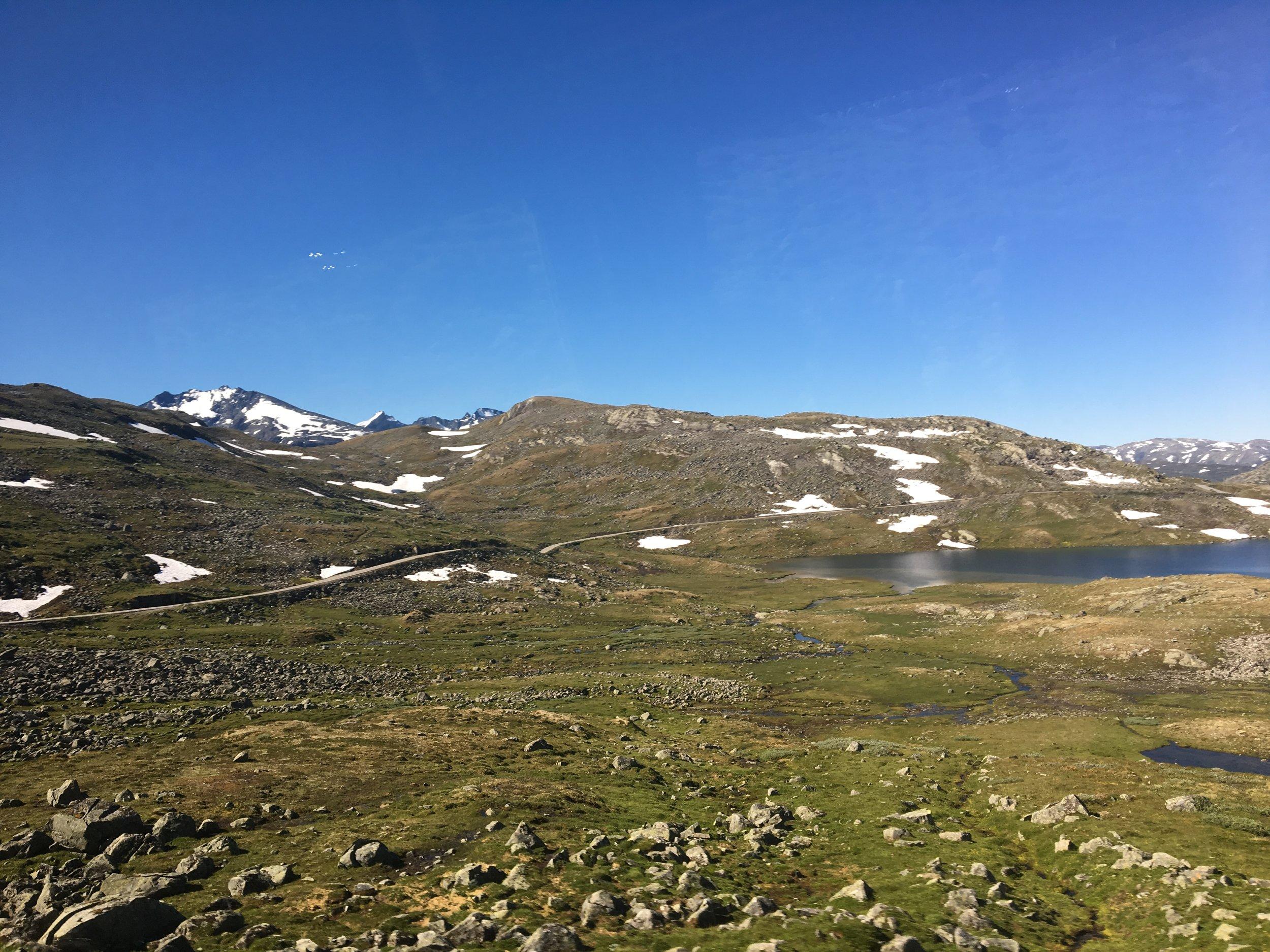 Fra bussvinduet: Sognefjellsveien med Fannaråken,Store Ringstind og Soleibotntindane lenger bak.