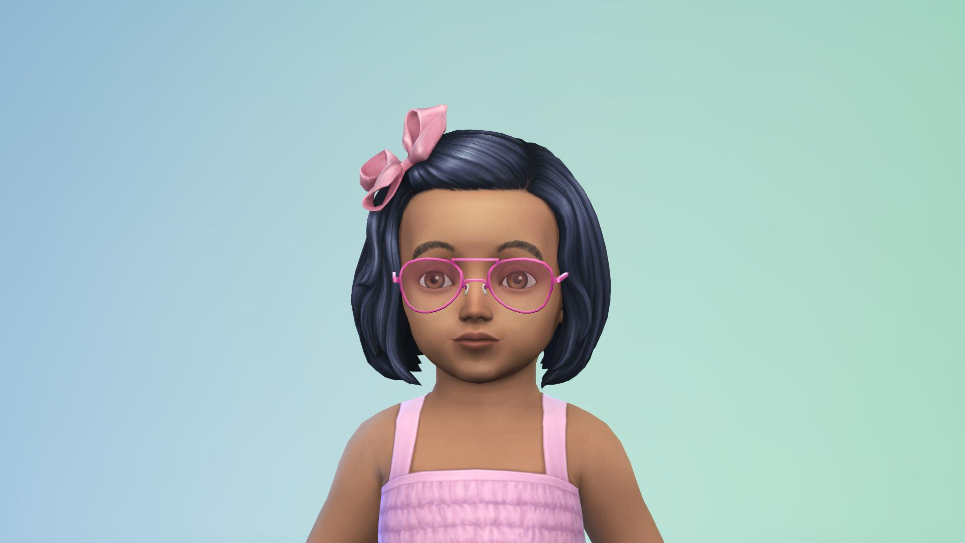 A cute toddler Sim with black hair and medium brown skin, pink glasses, a bow and a pink dress.
