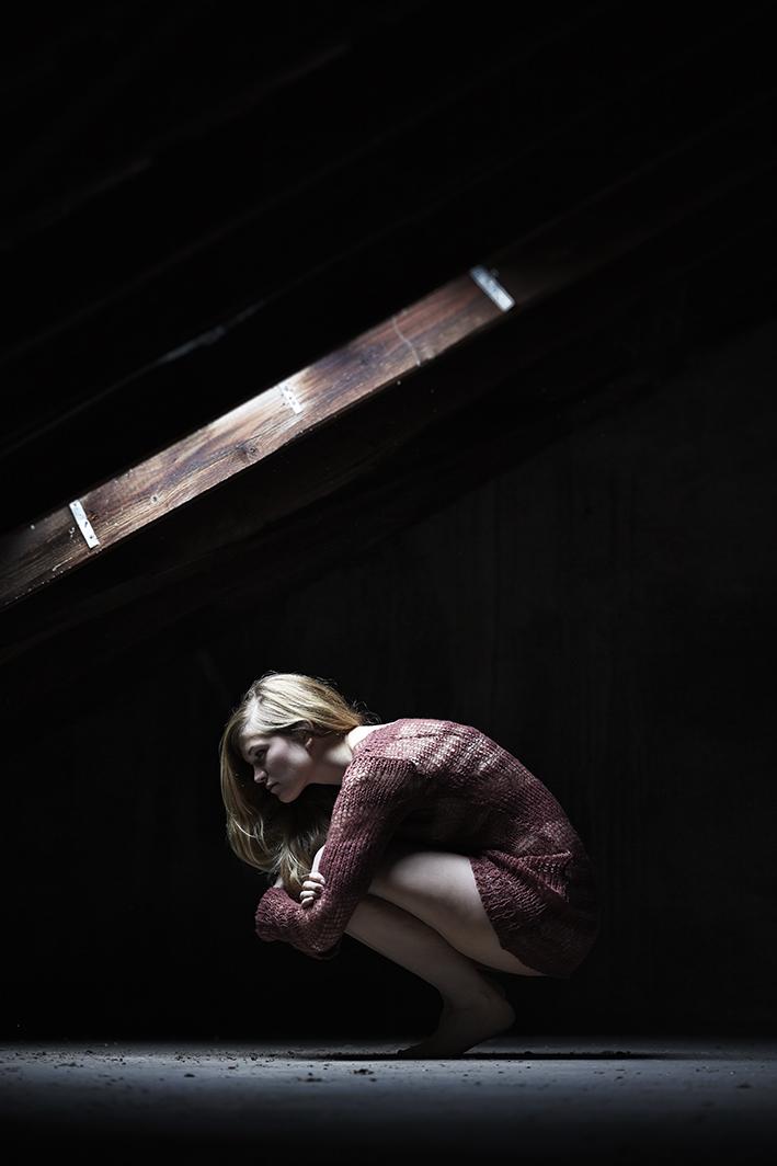 Portrait-Frau-hockt-unter-Dachfenster