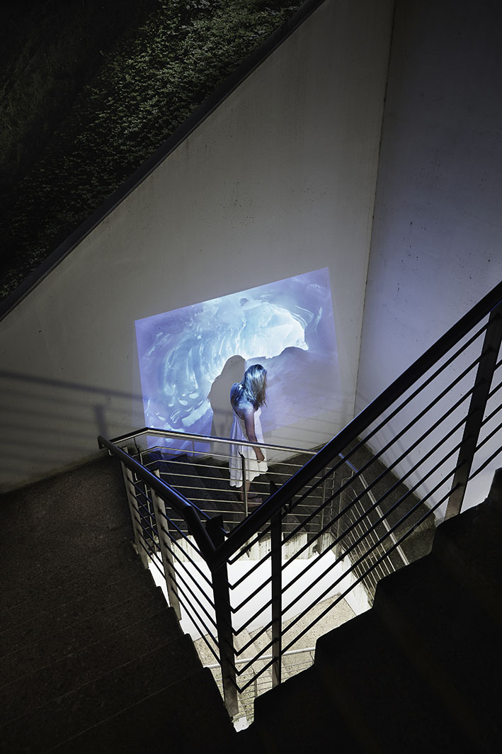 Projektion-Frau-steht-auf-Treppe-vor-Eishoehle