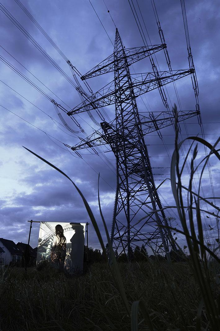 Projektion-Frau-steht-vor-angestrahlter-Leinwand-an-Strommast