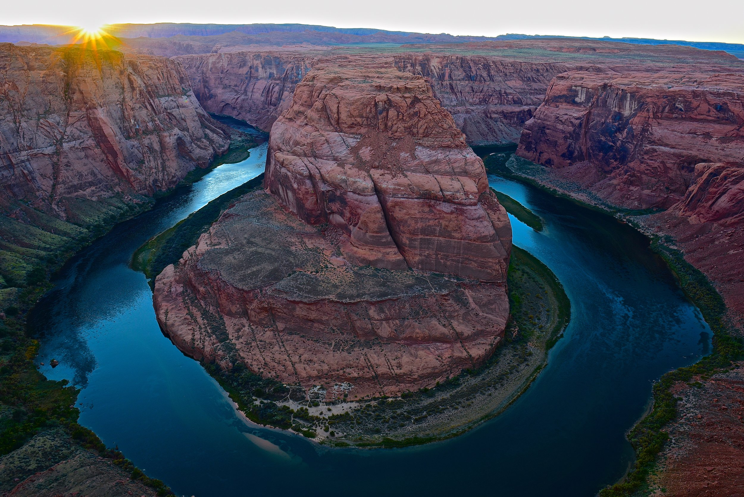 The sun bursting through just before it sets off in the horizon at Horseshoe Bend
