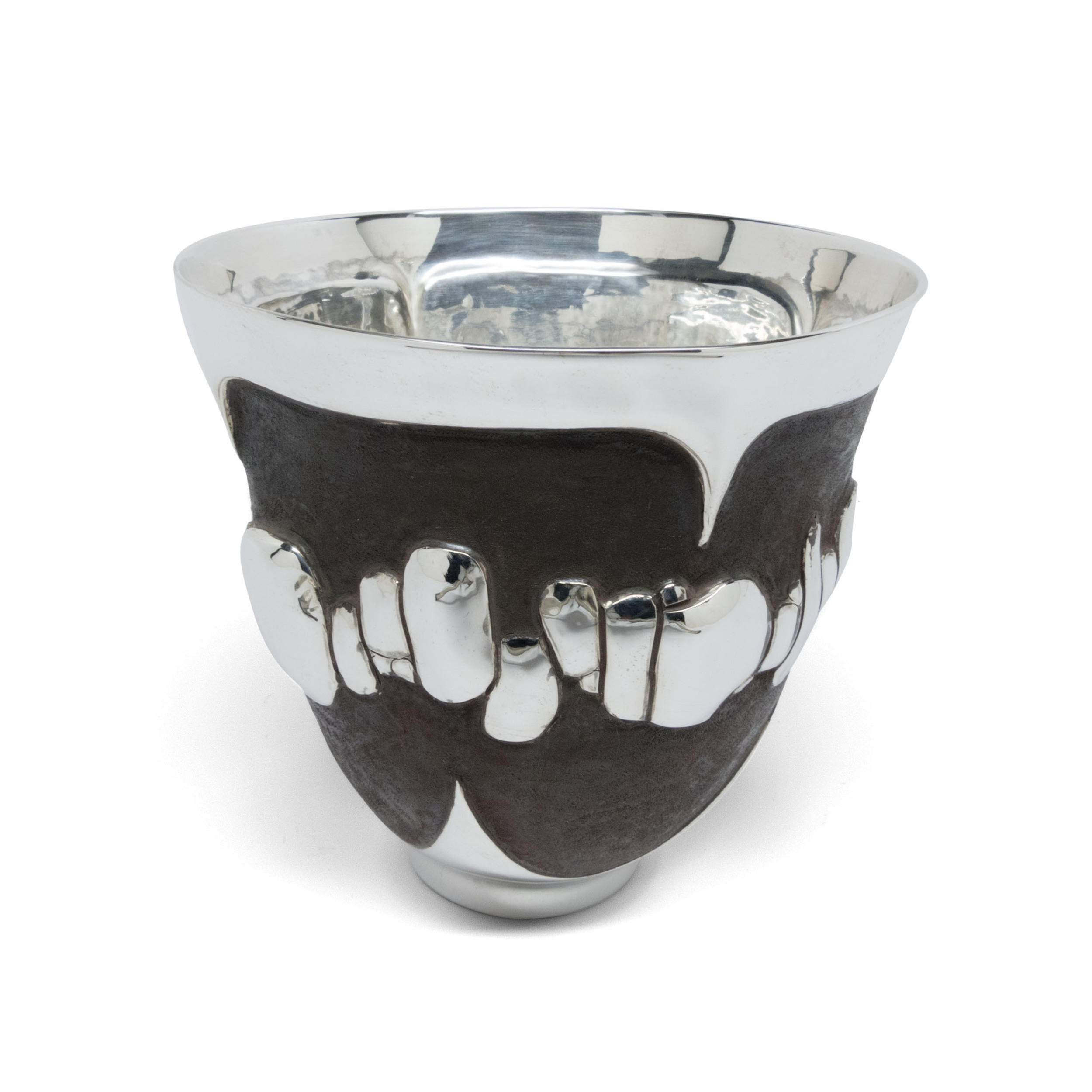 Sterling Silver cups are handmade by raising sheets of silver into volumetric forms. Details and designs are chased &   repoussé   into the vessels. All work is done by hand.