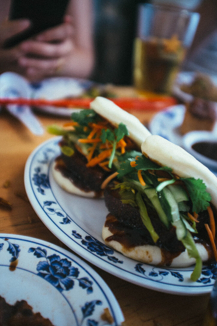 Pork belly baos with mustard greens, house-pickled carrots and cucumbers, and cilantro