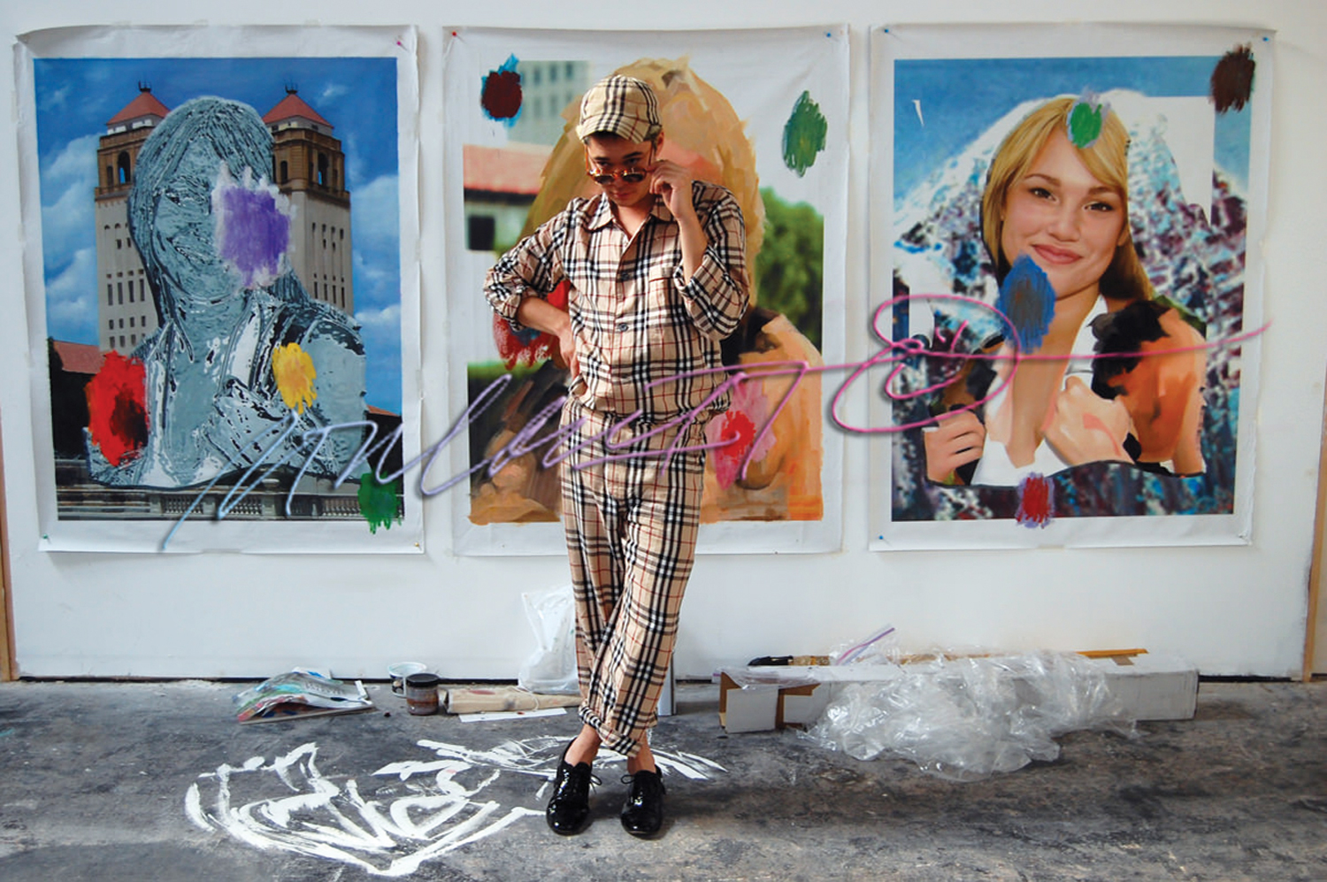 Parker Ito posing in his studio, in front of The Most Infamous Girl in the History of the Internet / Attractive Student / Parked Domain Girl, 2010 - 2013. Image courtesy of Artpulse Magazine.