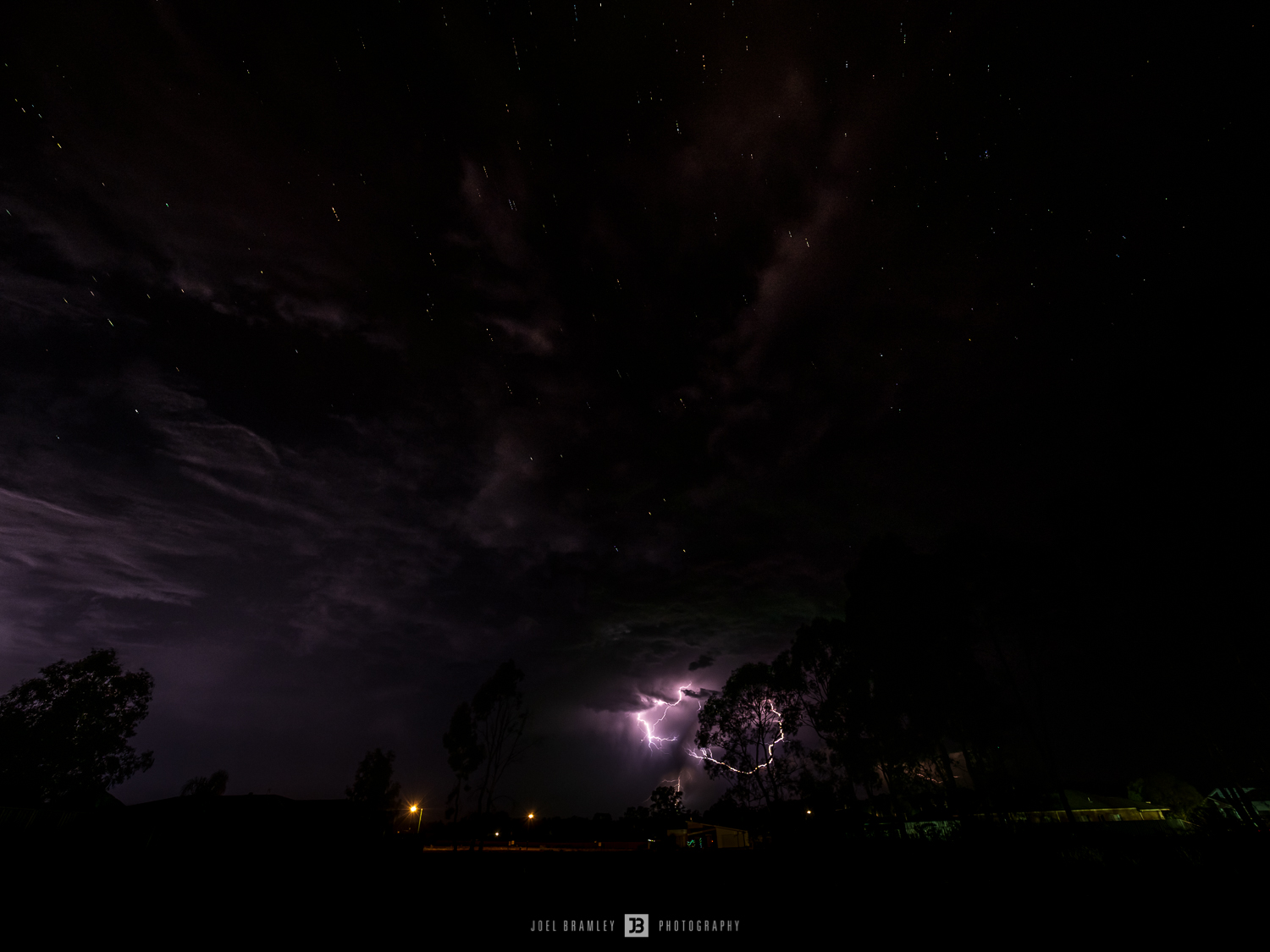 Distant lightning and stars through clouds