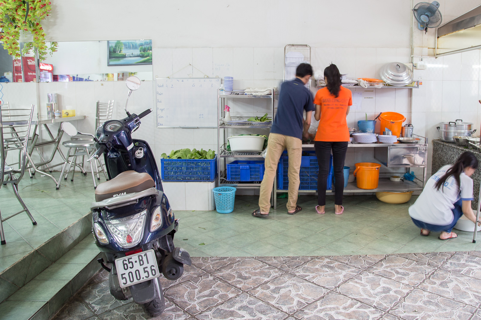 Customers park their scooters in the kitchen of Banh Cong Co Ut.