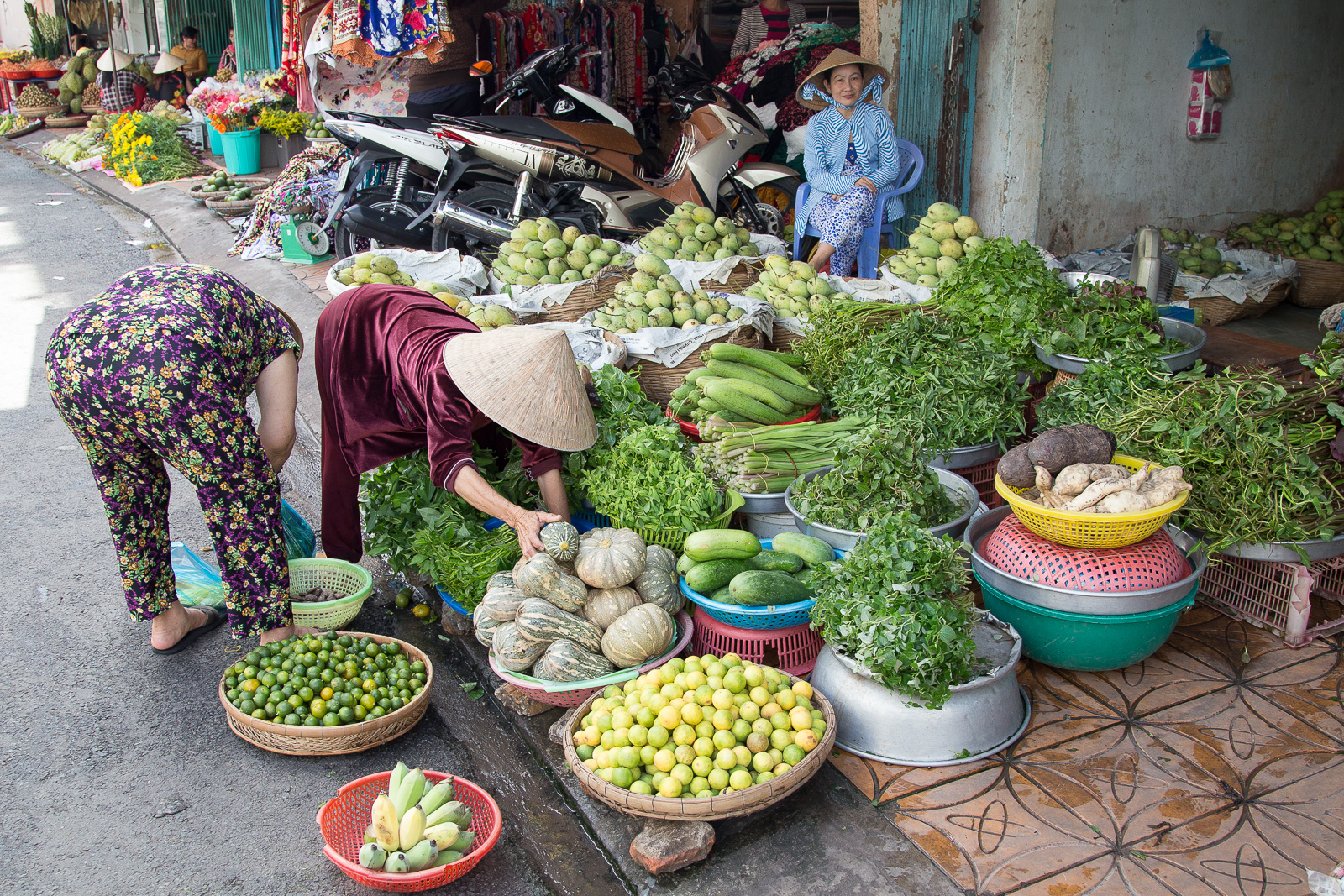 Fresh produce in abundance at the wholesale markets in Can Tho, Vietnam. We particularly like the lady in blue's psychedelic fashions.