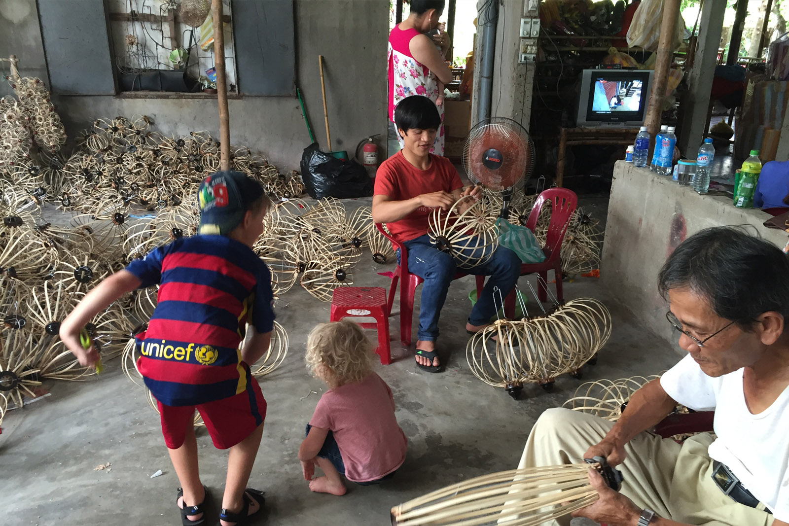 Older brother Ziggy taking Alby on a tour of the Ha Linh lantern factory, Hoi An, Vietnam