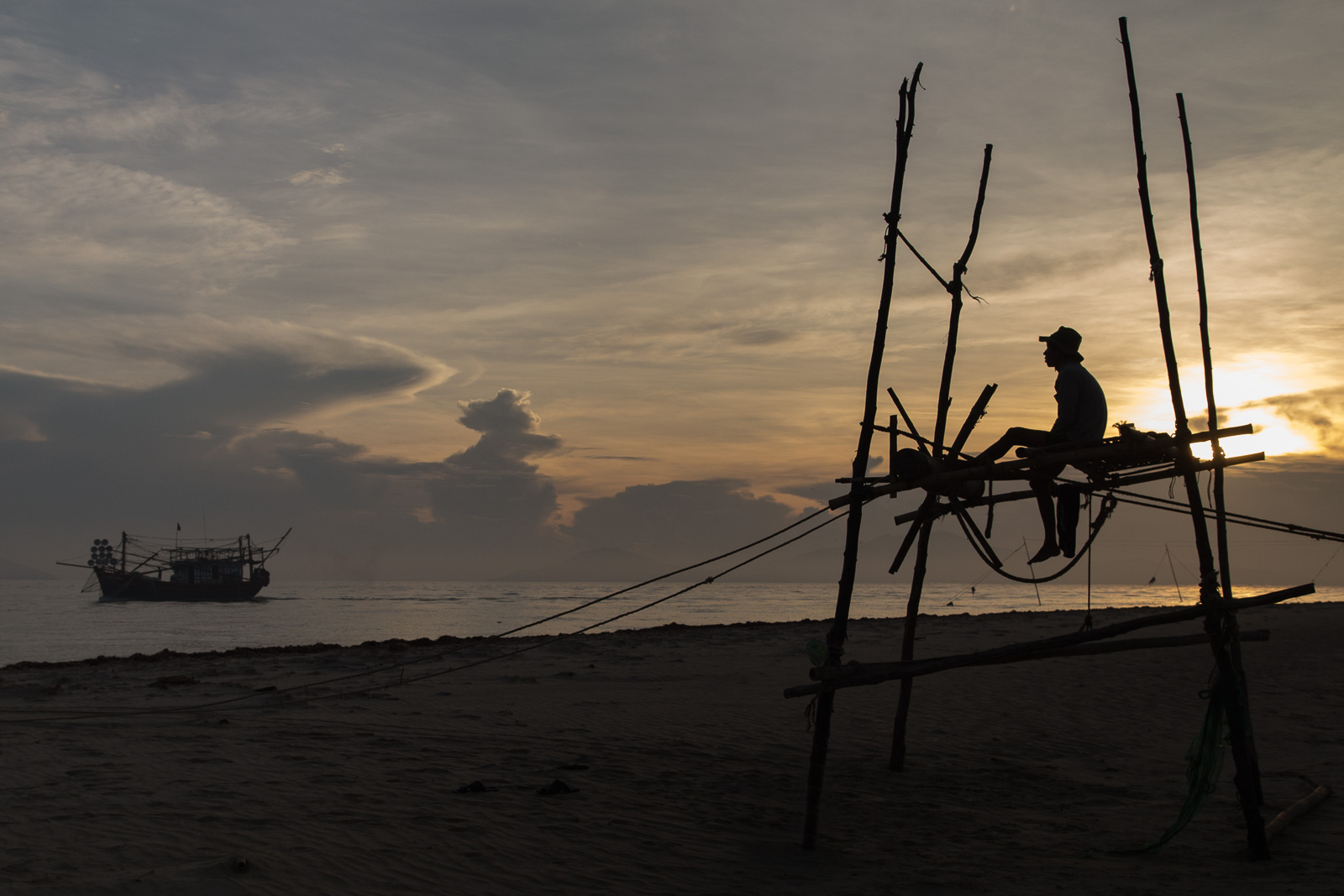 A fisherman waits patiently and watches the water for signs of movement. Once he senses that the fish have moved through he winds the winch up to check on his net.