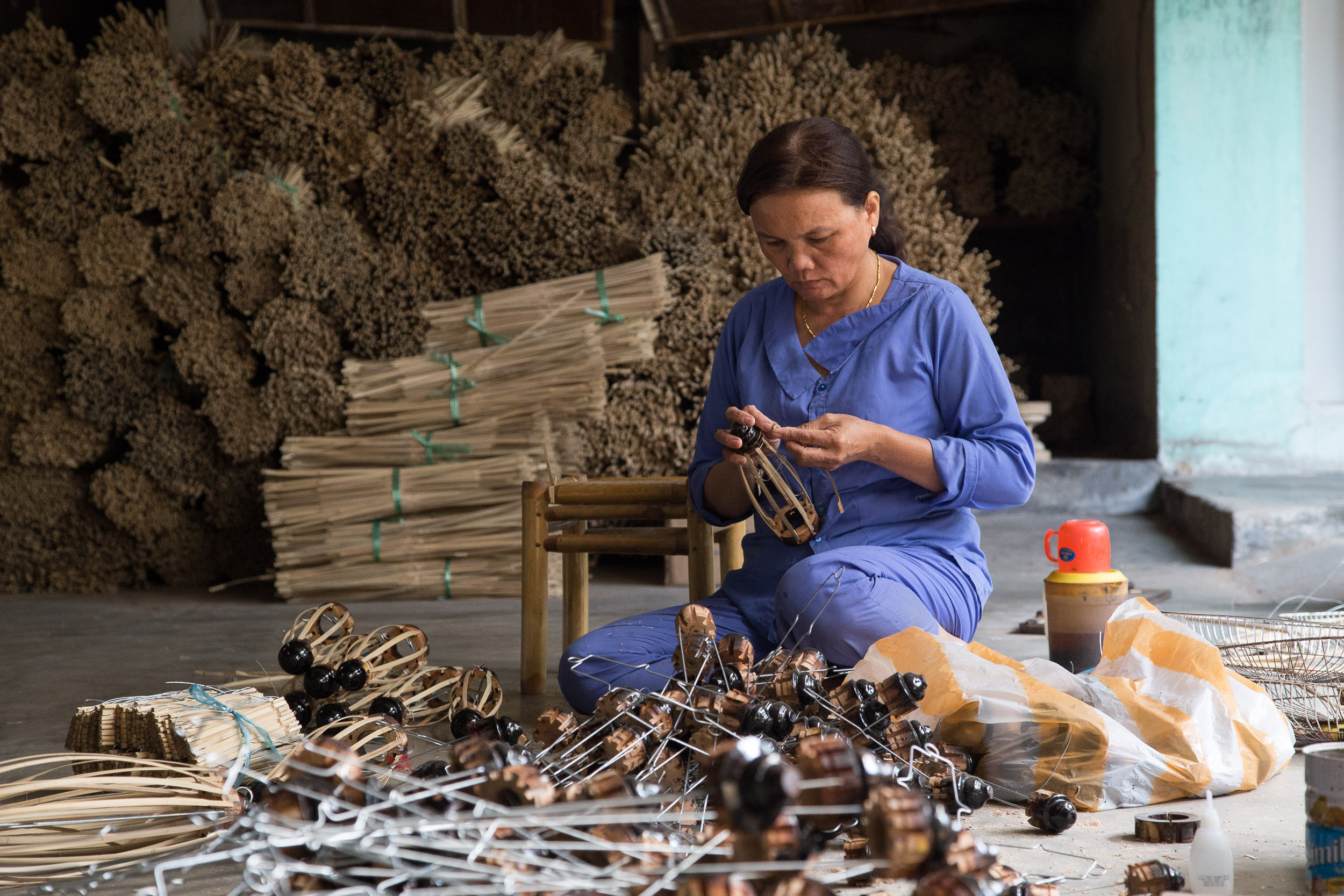 A worker constructing bamboo lantern frames at Hoi An's largest lantern factory, Ha Linh.
